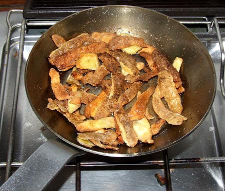 neue Eisenpfanne beim Einbraten mit Kartoffelschalen